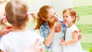 Kvinne som hjelper et barn å pusse tennene