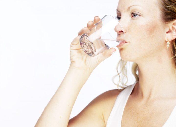 Kvinne som drikker et glass med vann
