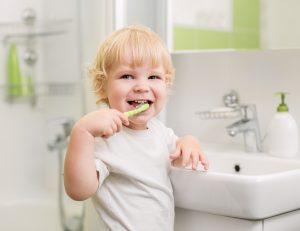 Glad barn som pusser tennene