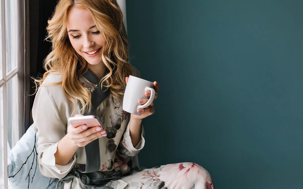 Rødhåret kvinner drikker kaffe og ser på mobilen
