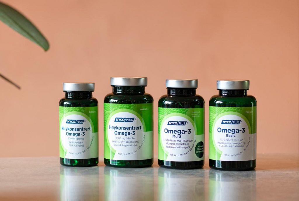 Fire ulike omega-3 produkter foran plante og ferskenfarget vegg.