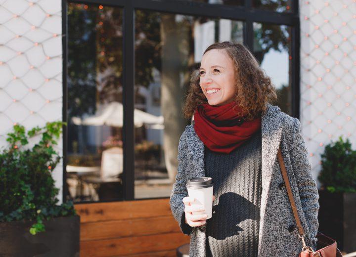 En smilende gravid kvinne med kåpe og kaffe utenfor en kafè