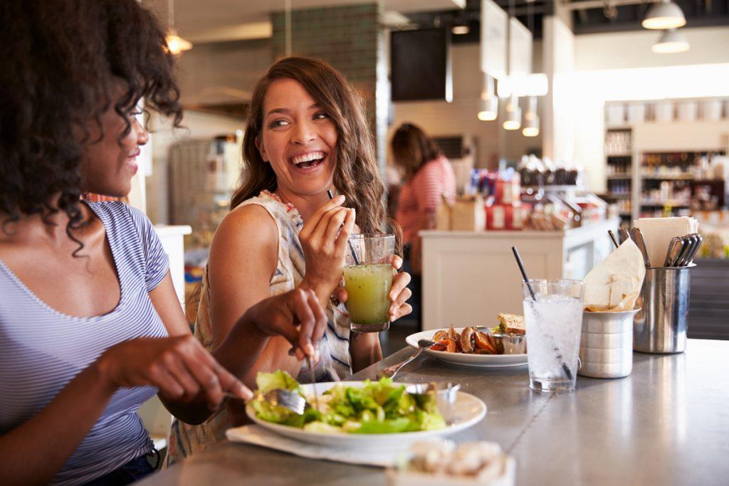Kvinner spiser salat og smiler