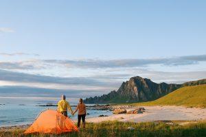 Par står med oppslått telt ved en strand i Lofoten.