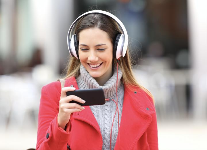 Kvinne i rød kåpe med headset som ser på noe på mobilen